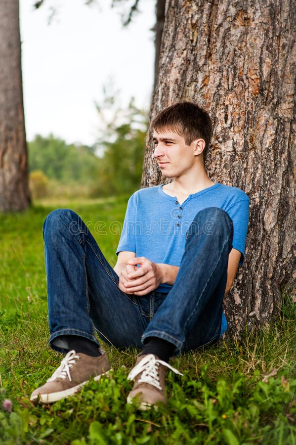 Young Man Under Tree. Young Man sit under the Tree in the Park stock photo