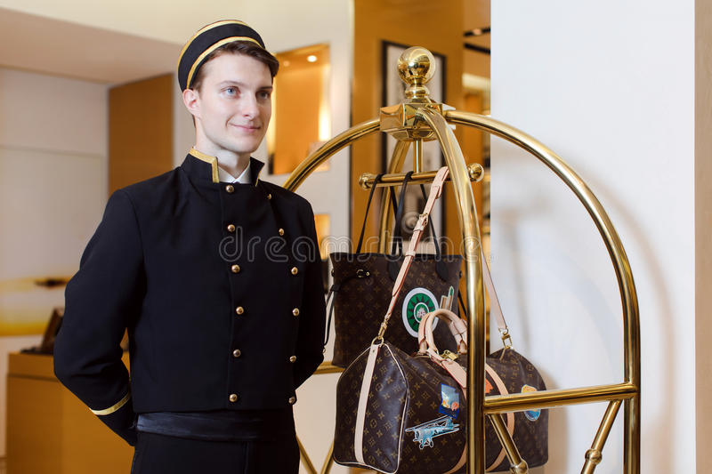 Young man in uniform serving in hotel royalty free stock photos