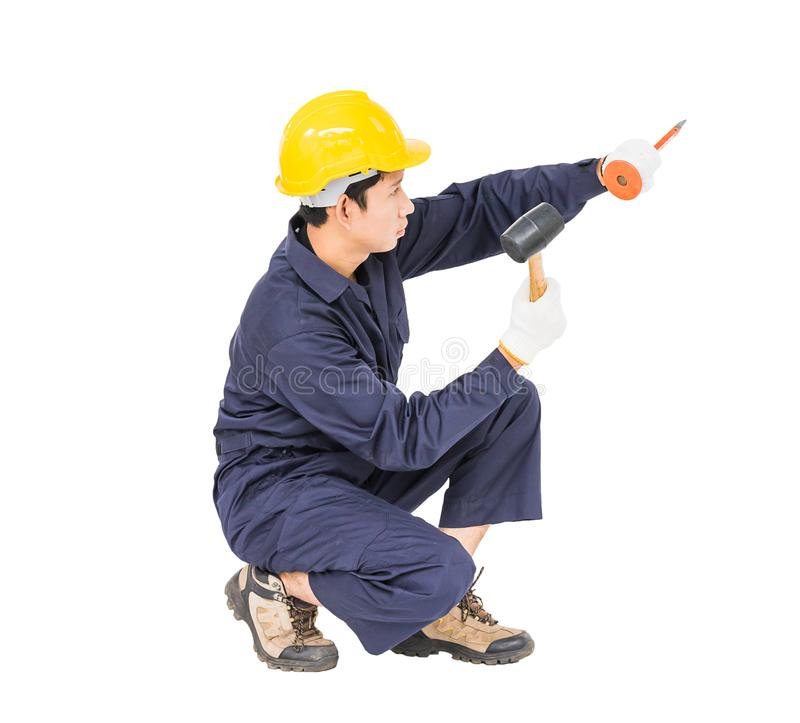 Man hold hammer and cold chisel on white. Young man in uniform sit and holding hammer was nailed to a cold chisel, Cut out isolated on white background royalty free stock photos