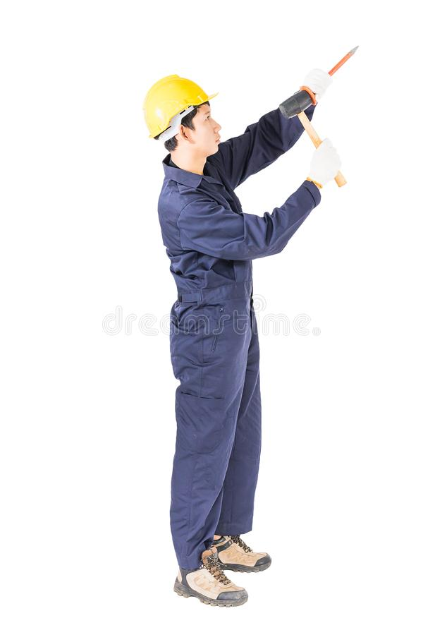 Man hold hammer and cold chisel on white. Young man in uniform sit and holding hammer was nailed to a cold chisel, Cut out isolated on white background royalty free stock image