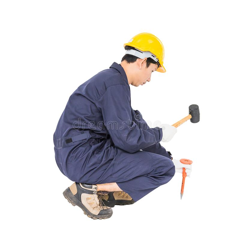 Man hold hammer and cold chisel on white. Young man in uniform sit and holding hammer was nailed to a cold chisel, Cut out isolated on white background stock photo