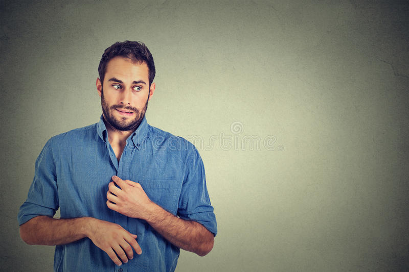 Young man in unpleasant, awkward situation, playing nervously with hands. Embarrassment. Portrait young man opening shirt to vent, it's hot, unpleasant, awkward stock photography