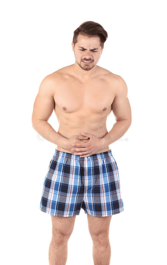 Young man with urological problems suffering from pain. On white background stock image