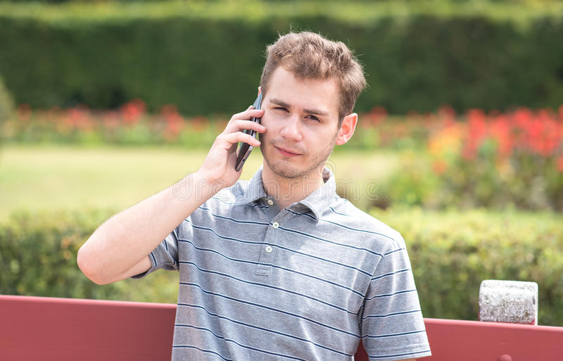 Young man use a phone in the park stock images