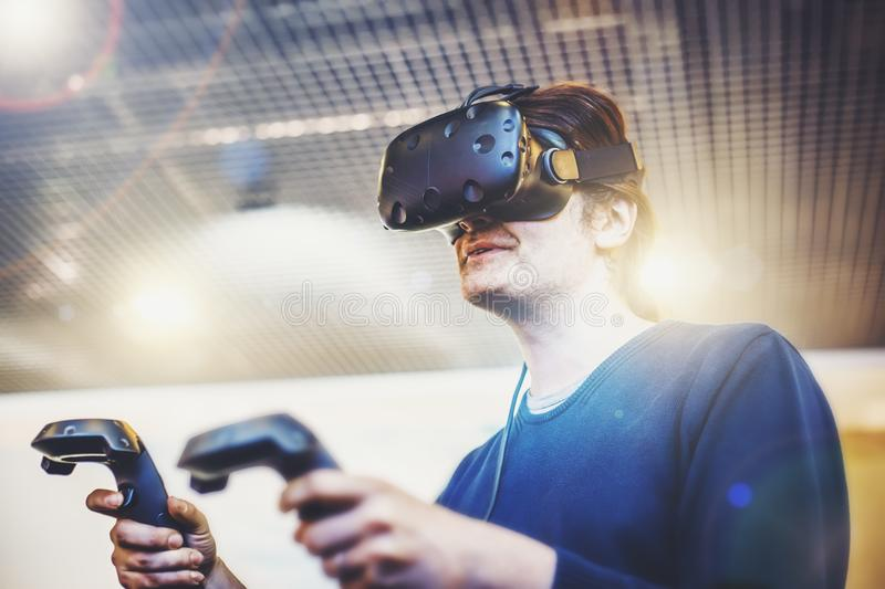 Young man use virtual reality goggles or VR headset or helmet, play videogame with wireless controllers in hands stock image