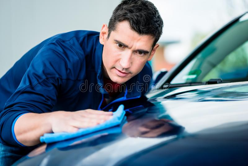 Man using an absorbent towel for drying the surface of a car royalty free stock images