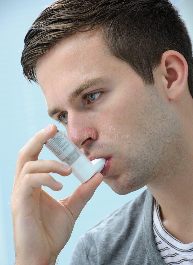 Young man using an asthma inhaler stock images