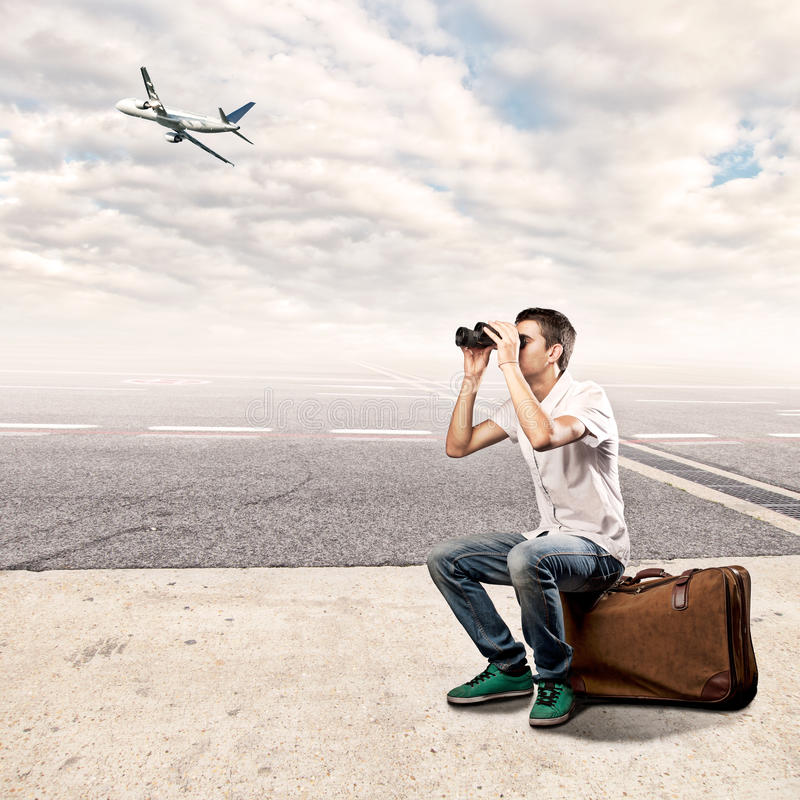 Young man using binoculars at the airport. Young man sitting on a suitcase and using binoculars at the airport royalty free stock photos