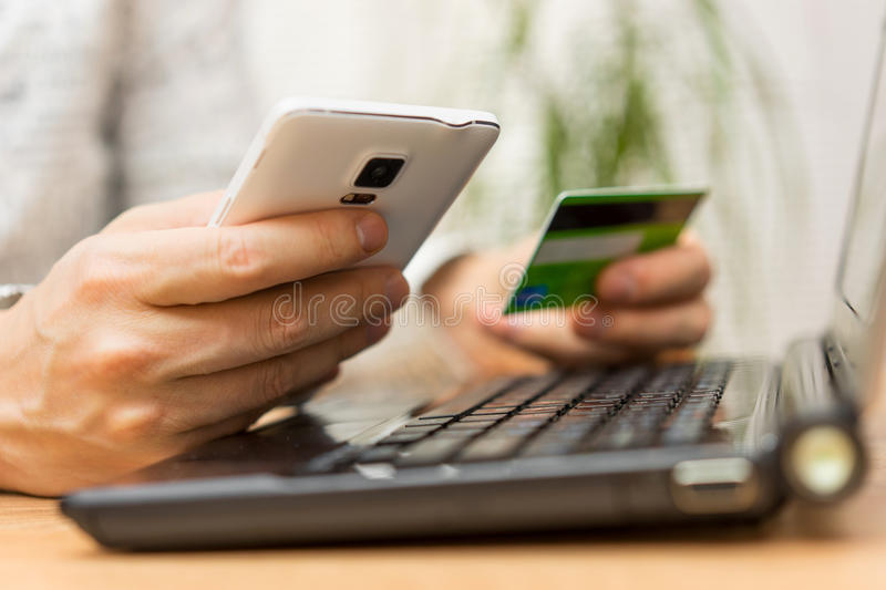 young man is using credit card for online shopping on smart phone and laptop computer royalty free stock photos