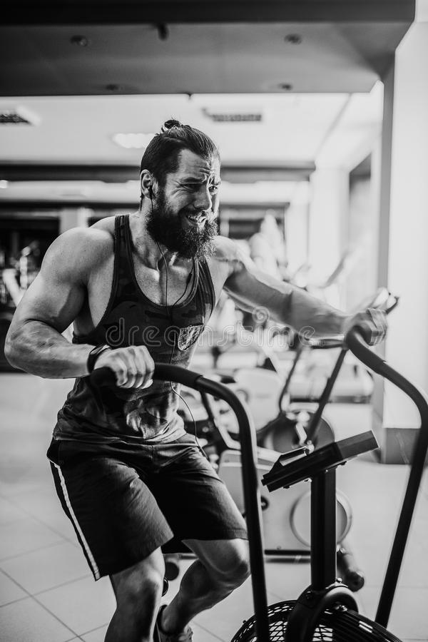 Young man using exercise bike at the gym. Fitness male using air bike for cardio workout at crossfit gym. royalty free stock photography