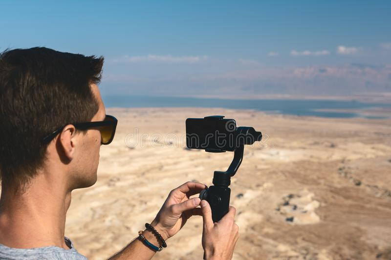 Young man using gimbal in the desert of israel stock photography
