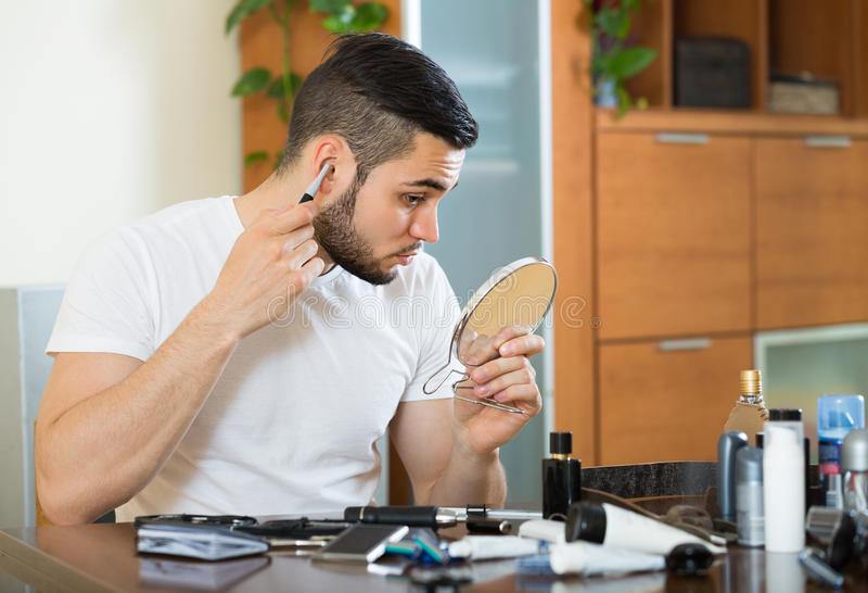 Young man using hair trimmer royalty free stock image