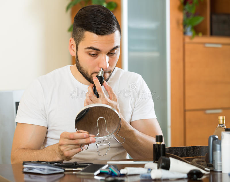 Young man using hair trimmer. Young man using trimmer for removing hair in his nose at home royalty free stock image