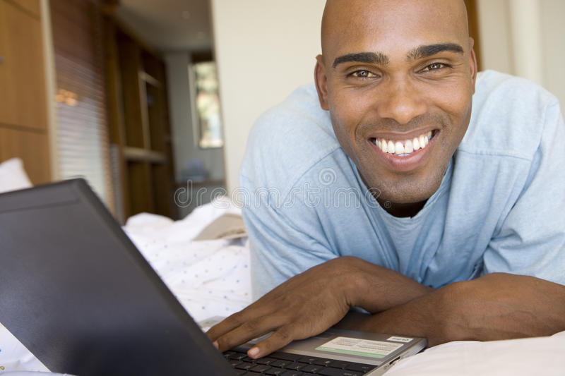 Young man using laptop on bed, smiling, portrait royalty free stock photography