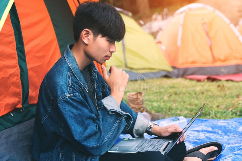 Young man using laptop during camping in the morning stock image