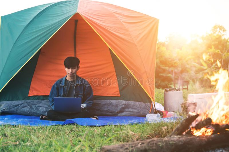 Young man using laptop during camping in the morning stock photo