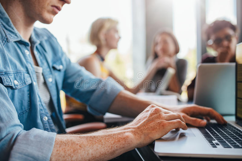Young man using laptop with classmates studying in background stock images