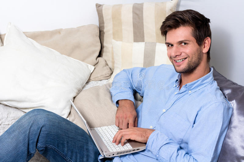 Download Young Man Using Laptop On Couch Stock Image - Image: 28077779