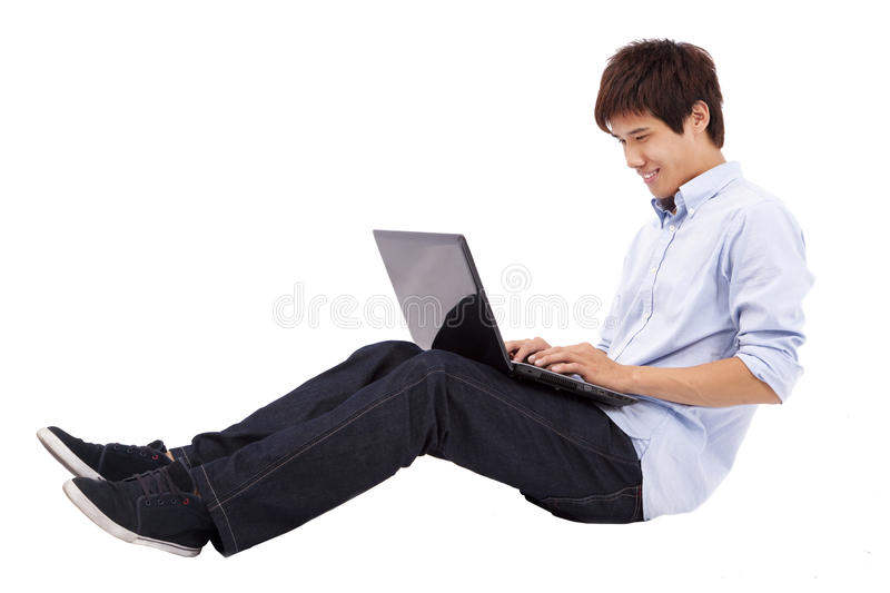 Young man using laptop on the floor. Happy and relax young man using laptop on the floor isolated on white background stock image