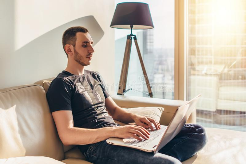 Young man using laptop while sitting on a sofa stock photos