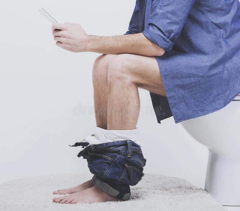 Young man using laptop on toilet. royalty free stock image