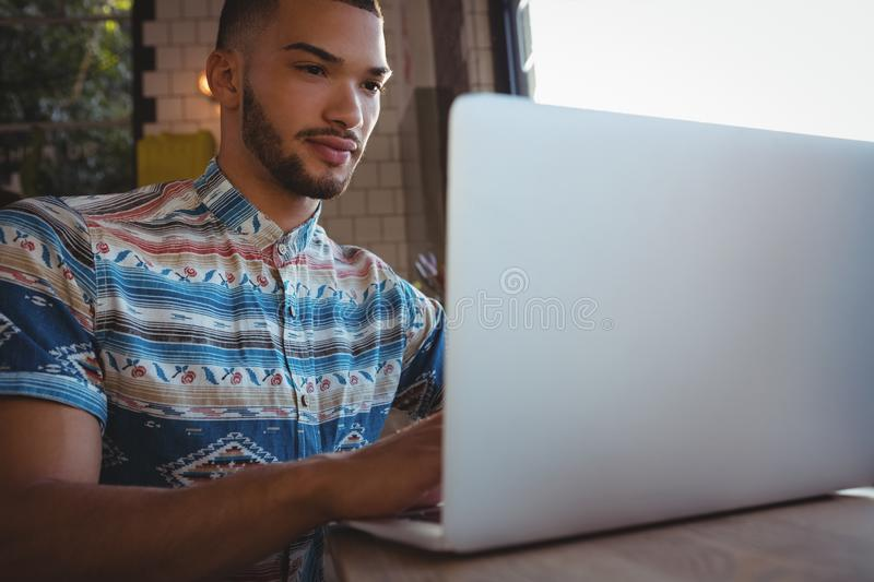 Young man using laptop in cafe royalty free stock image