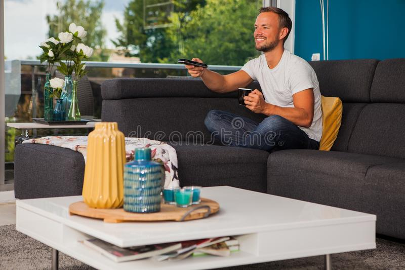 Young man using a remote control while drinking coffee on the couch stock images