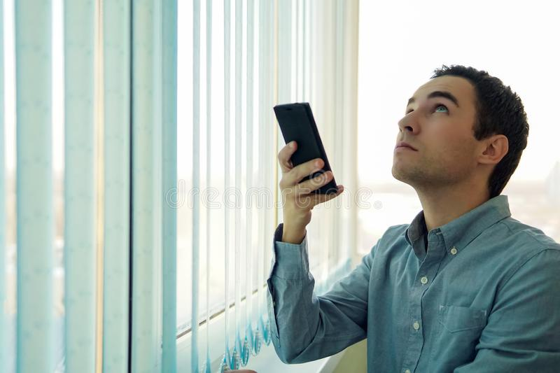 Young man using a smartphone in front of a window. stock photos