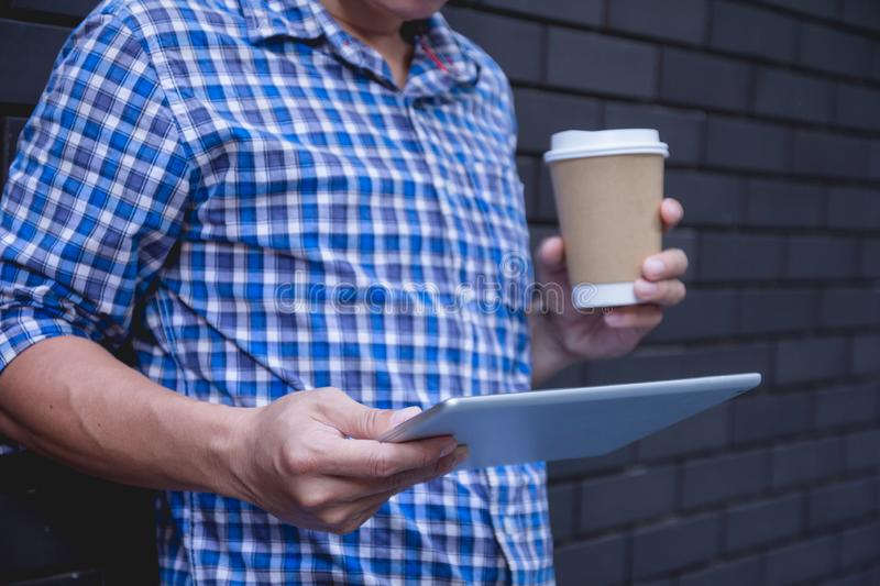 Young man using tablet computer holding coffee cup on street wall with copy space. royalty free stock image