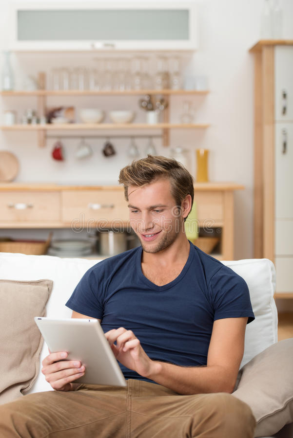 Download Young Man Using A Tablet At Home Stock Photo - Image: 33601864