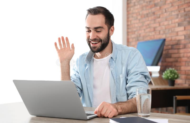Young man using video chat on laptop. In home office stock photo