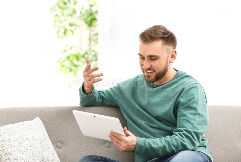 Young Man Using Video Chat On Tablet In Room Stock Photo