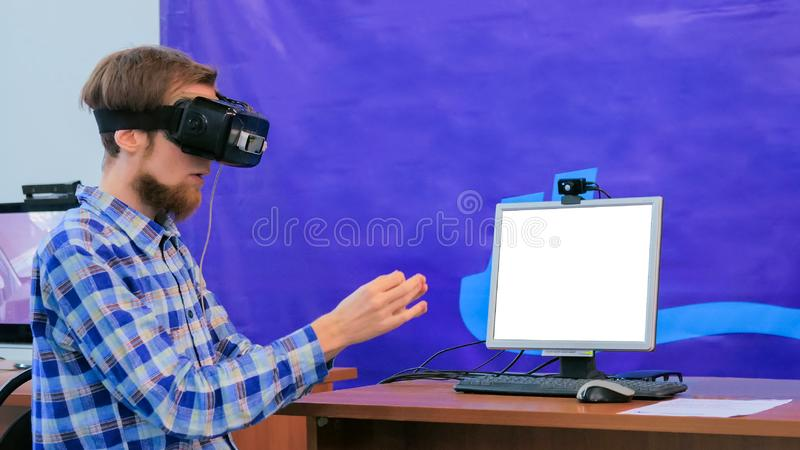 Young man using virtual reality headset in front of white blank monitor royalty free stock images