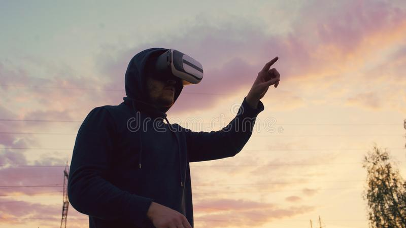 Young man using VR 360 headset and having vitrual reality experience at city park on sunset royalty free stock image