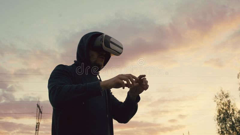 Young man using VR 360 headset and having vitrual reality experience at city park on sunset stock photography