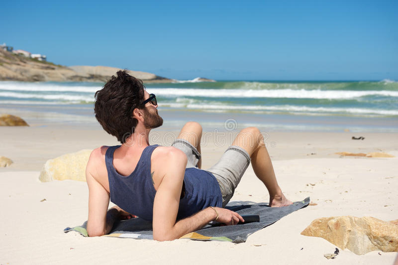 Young man on vacation sitting alone at a secluded beach. Rear portrait of a young man sitting alone at a secluded beach on vacation stock photos