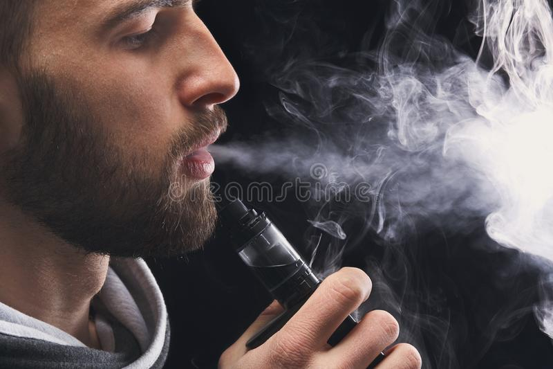 Young man vaping e-cigarette with smoke on black royalty free stock photography