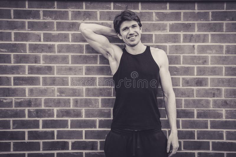 Young man in vest top flexing biceps royalty free stock images