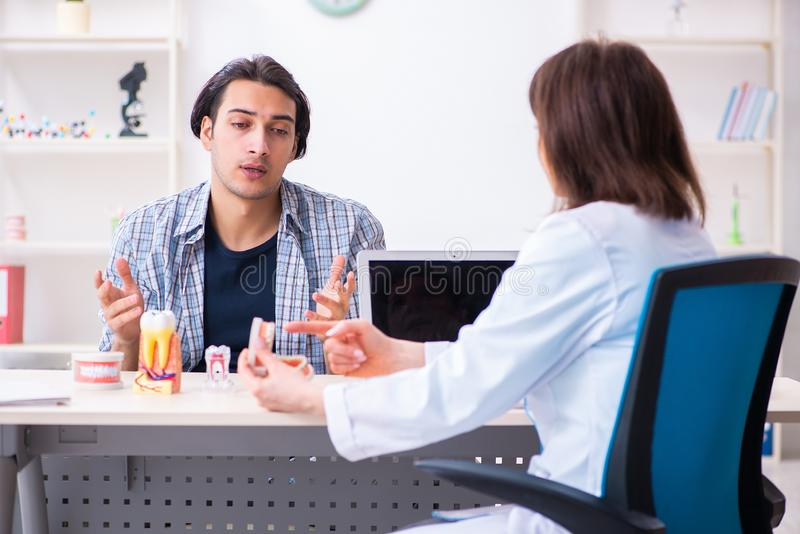 Young man visiting female doctor stomatologist. The young men visiting female doctor stomatologist royalty free stock photos