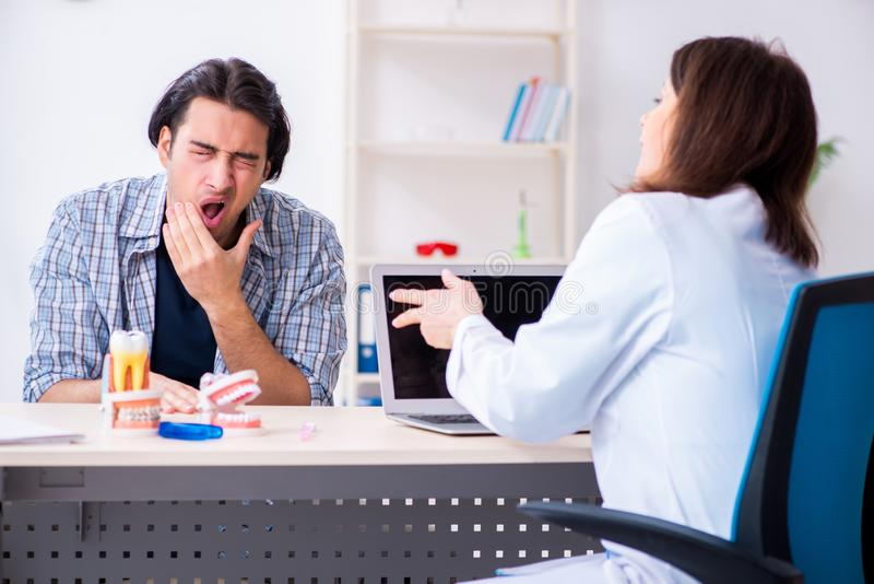 Young man visiting female doctor stomatologist. The young men visiting female doctor stomatologist stock photography