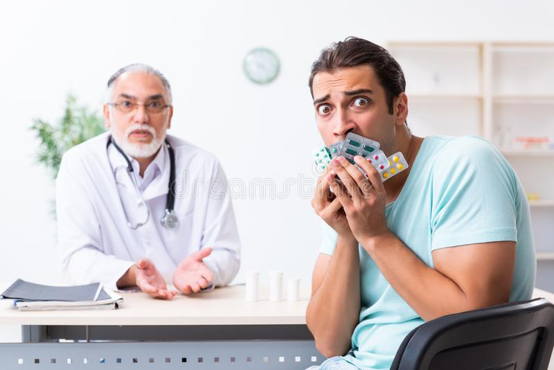 Young man visiting old male doctor. The young men visiting old male doctor royalty free stock image