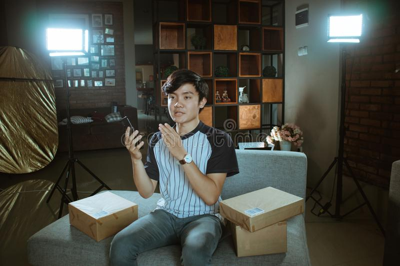 Young man vlogger make video review about of new type smartphone series stock photo