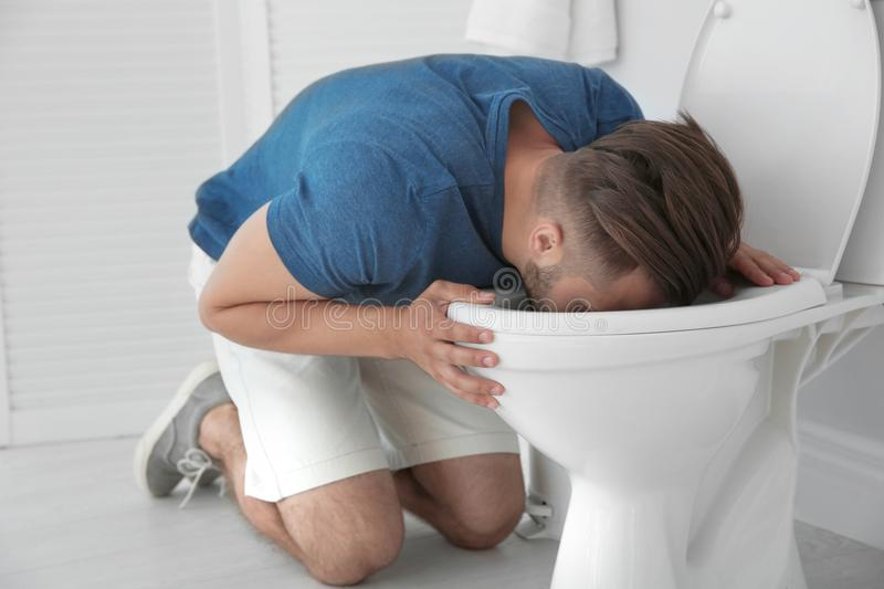 Man vomiting in toilet bowl at home. Young man vomiting in toilet bowl at home royalty free stock photo