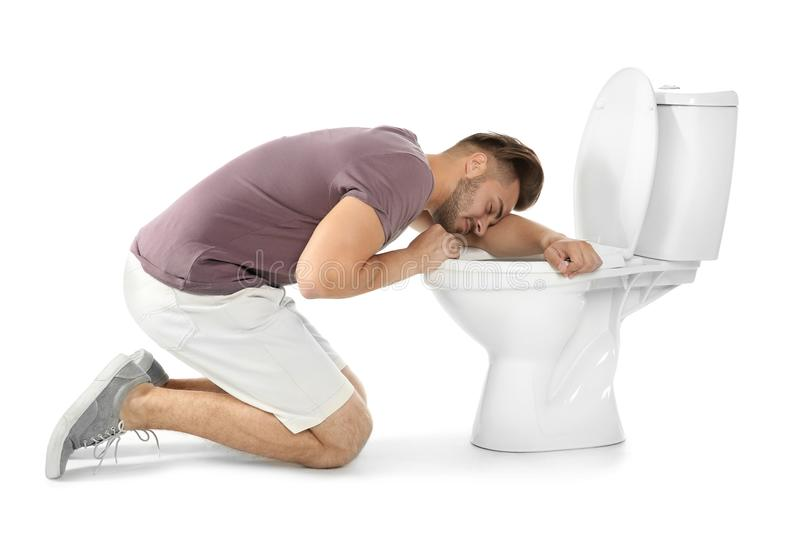 Young man vomiting in toilet bowl. On white background royalty free stock image