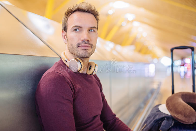Young man waiting listening music and using mobile phone at the stock image
