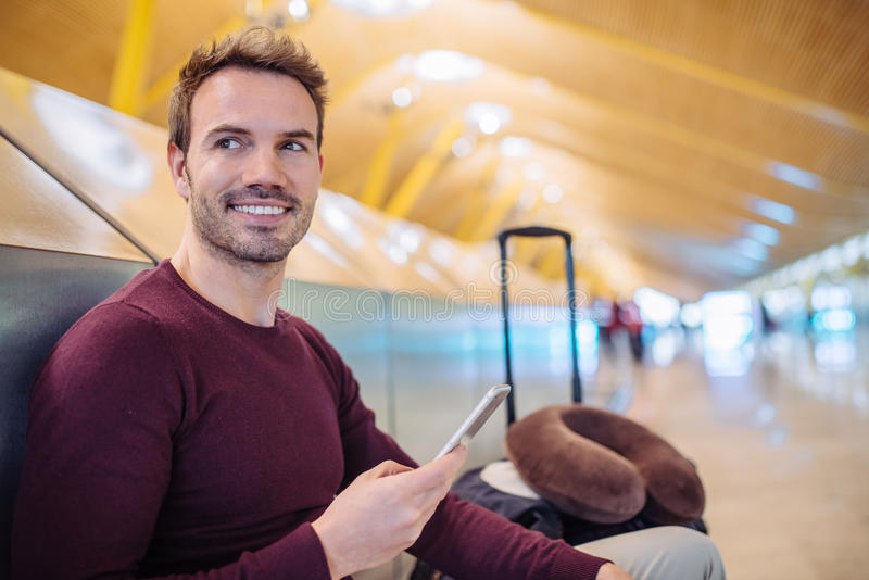 Young man waiting listening music and using mobile phone at the stock photo