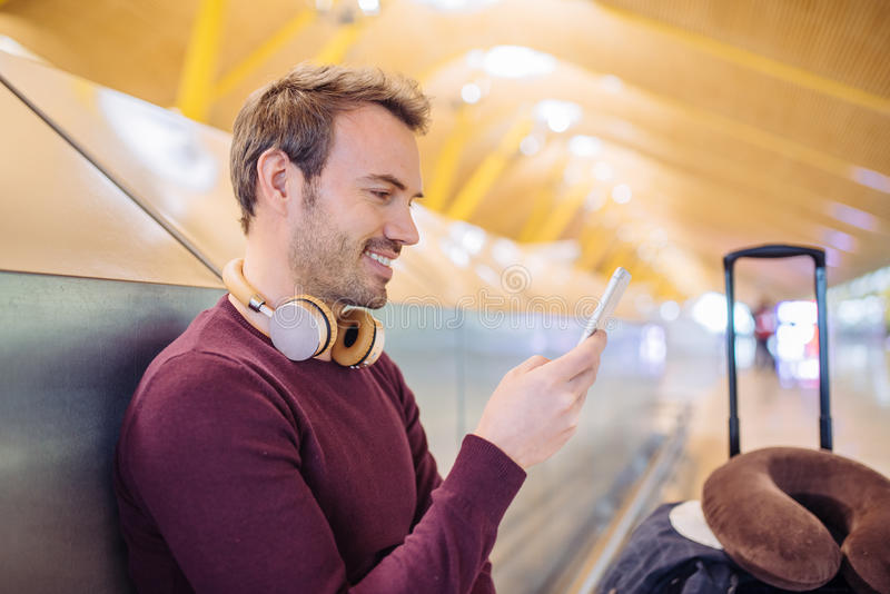 Young man waiting listening music and using mobile phone at the stock photography