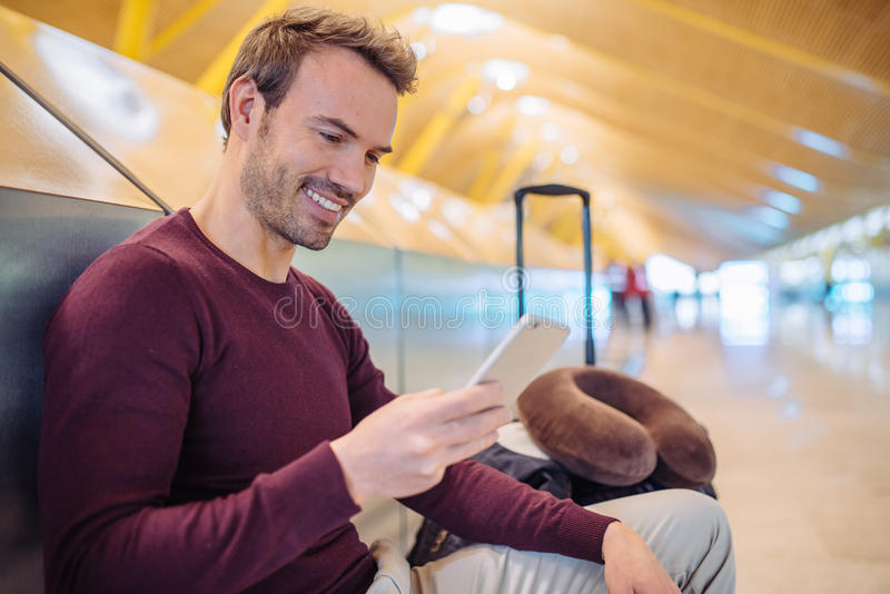Young man waiting using mobile phone at the airport with a suitcase stock photo