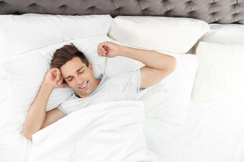 Young man waking up in bed with pillows. At home royalty free stock images