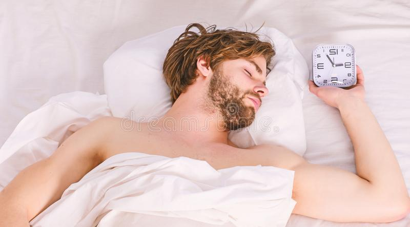 A young man waking up in bed and stretching his arms. Man feeling back ache in the bed after sleeping. Man on bed. A young man waking up in bed and stretching stock photo